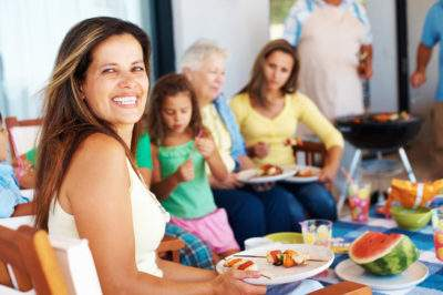 woman eating with friends and family at company picnic